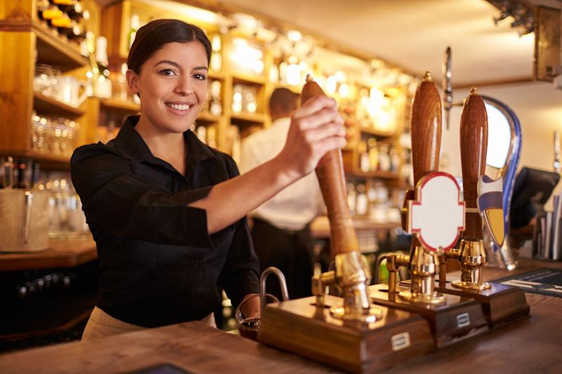 A young woman working behind a bar looking to camera, horizontal