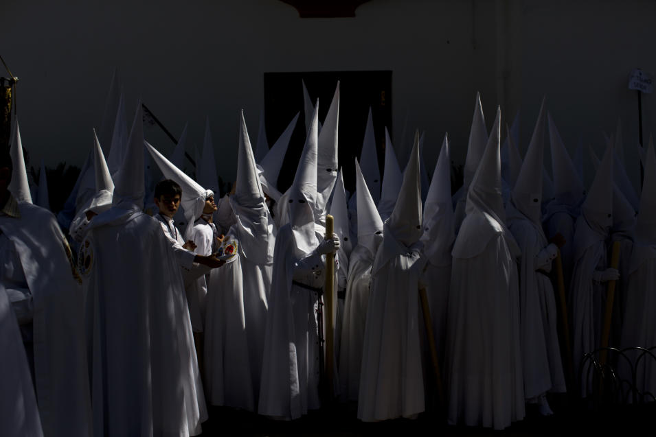 Penitents from La Paz brotherhood wait outside the church before taking part in a procession in Seville, Spain, Sunday, March 24, 2013. Hundreds of processions take place throughout Spain during the Christian Easter Holy Week. (AP Photo/Emilio Morenatti)
