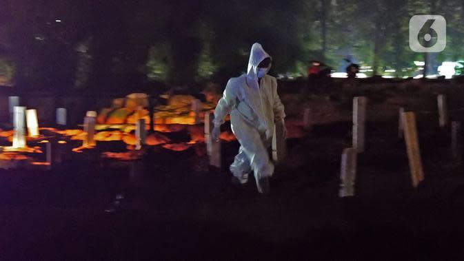 Petugas pemakaman mengenakan hazmat saat memakamkan jenazah pasien COVID-19 di TPU Pondok Ranggon, Jakarta, Selasa (14/7/2020). Hingga hari ini, lima provinsi mencatat tambahan kasus baru tertinggi yakni Jatim, DKI Jakarta, Sulsel, Kalsel, dan Sumut. (Liputan6.com/Herman Zakharia)