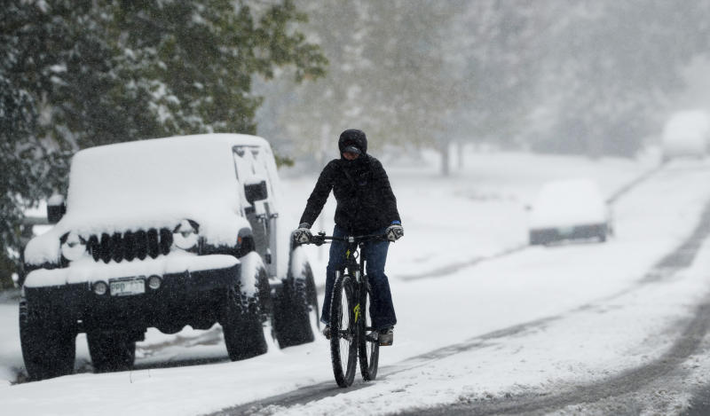 FILE - In this Oct. 10, 2019, file photo, a bicyclist uses a tire track to guide her bicycle down South Monroe Street as the season's first snow storm sweeps over the metropolitan area in Denver. A government agency is recommending that all 50 states enact laws requiring bicyclists to wear helmets to stem an increase in bicycle deaths on U.S. roadways. The recommendation was among several issued by the National Transportation Safety Board after a hearing Tuesday, Nov. 5, on bicycle safety. (AP Photo/David Zalubowski, File)