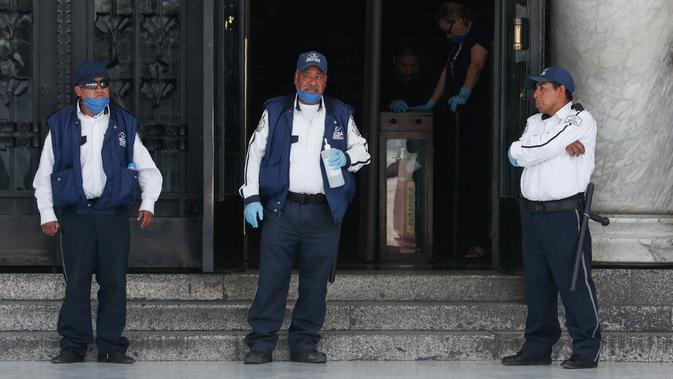 Penjaga berdiri di depan pintu masuk Palace of Fine Arts yang ditutup untuk umum di Mexico City (23/3/2020). Pemerintah kota mengumumkan langkah-langkah untuk menangani COVID-19 seperti menutup bar, disko, museum, kebun binatang, bioskop, teater dan gym mulai Senin. (AP Photo/Rebecca Blackwell)