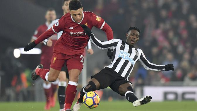 Aksi pemain Liverpool, Alex Oxlade-Chamberlain (kiri) saat berebut bola dengan pemain Newcastle United, Christian Atsu pada lanjutan Premier League di Anfield, Liverpool, (3/3/2018). Liverpool menang 2-0. (Anthony Devlin/PA via AP)