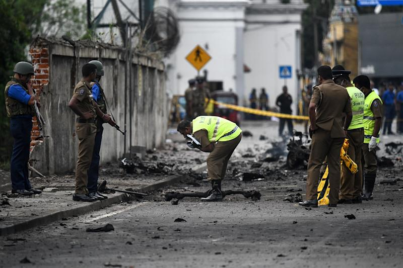 Sri Lankan security personnel inspect the debris of a car after it explodes when police tried to defuse a bomb near St Anthony's Shrine in Colombo on Monday. Source: Getty Images