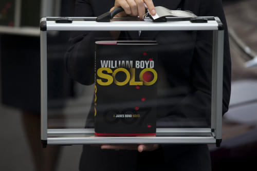 "A flight attendant poses for photographers with a copy of the new James Bond novel ""Solo"" during a launch photocall outside the Dorchester Hotel in London, Wednesday, Sept. 25, 2013. ""Solo"" is set in 1969 and takes the suave British spy, 45 years old and feeling his age, from London's plush Dorchester Hotel to a war-torn West African country and to Washington. (AP Photo/Matt Dunham)"