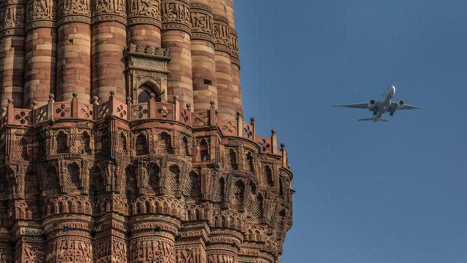 Pesawat terbang melintas dekat situs warisan dunia UNESCO Qutub Minar di New Delhi, India, Kamis (13/2/2020). Ayat Alquran yang terukir di bangunan Qutub Minar bersanding dengan karakter hiasan Parso-Arab dan Nagari. (Xinhua/Javed Dar)