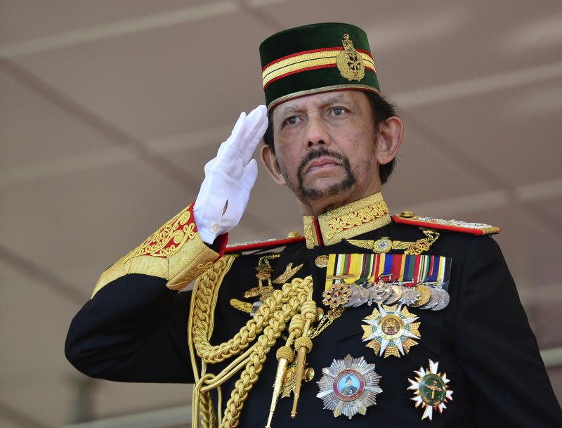 Brunei's Sultan Hassanal Bolkiah dressed in full military regalia salutes to an honor guard during his 73rd birthday celebrations in Bandar Seri Begawan, Brunei, Monday, July 15, 2019. (AP Photo/Ahim Rani)