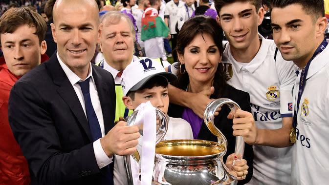 Pelatih Real Madrid, Zinedine Zidane bersama istrinya Veronique dan anak-anak mereka Enzo, Theo dan Elyaz memegang piala usai Real Madrid memenangkan pertandingan Liga Champions di Stadion Cardiff, Wales (3/6). (AFP Photo/Javier Soriano)