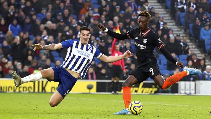 Pemain Brighton and Hove Albion, Lewis Dunk, berusaha menghadang tendangan striker Chelsea, Tammy Abraham, pada laga Premier League di Stadion AMEX, Rabu (1/1/2020). Kedua tim bermain imbang 1-1. (AP/(Gareth Fuller)