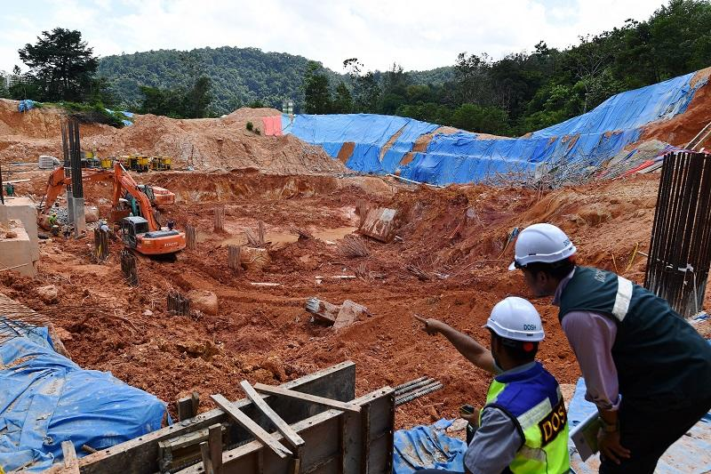 Workers from the Department of Occupational Safety and Health examine the site where the deadly landslide occurred at Tanjung Bungah, Penang October 24, 2017. — Bernama pic