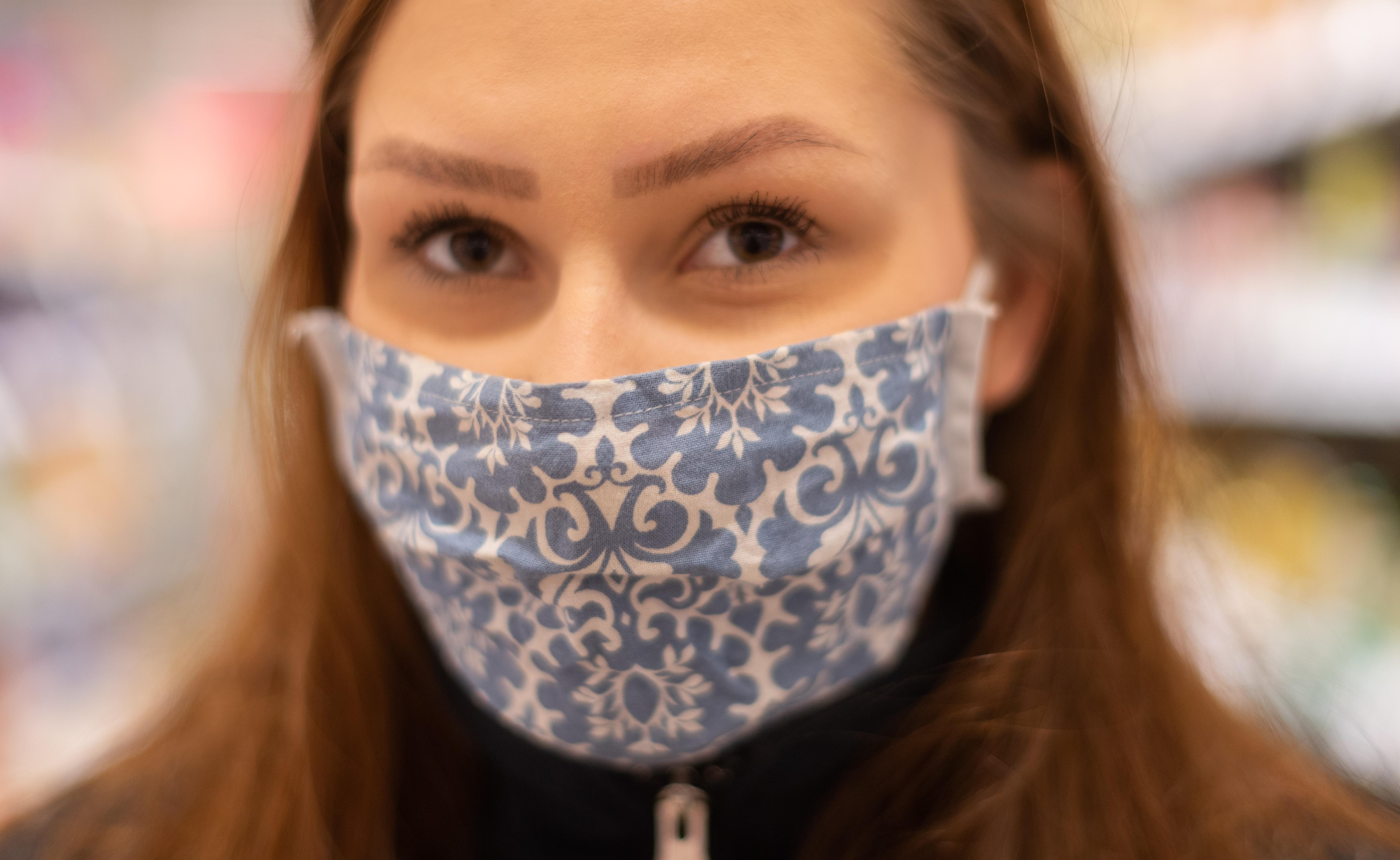 01 April 2020, Saxony, Dresden: Selina Schmidt, a third-year retail saleswoman trainee, is standing in a supermarket in the morning before opening time and wearing a protective mask. In order to slow down the spread of the coronavirus, the federal government has further considerably restricted public life. Photo: Robert Michael/dpa-Zentralbild/dpa (Photo by Robert Michael/picture alliance via Getty Images)