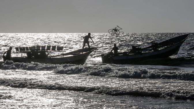 Seorang nelayan Palestina melempar tali dari perahu ke perahu lain saat menangkap ikan di Laut Mediterania, Rafah, Jalur Gaza, Rabu (2/9/2020). (SAID KHATIB/AFP)