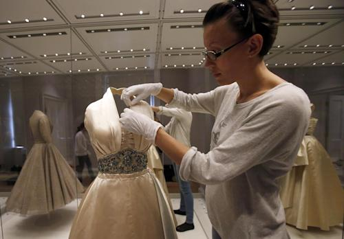 In this photo taken Monday July 1, 2013, an employee fixes a dress worn by Princess Margaret to a film premier in London and to a dinner in Paris as a guest of Prince Paul of Yugoslavia in 1951, at the Fashion Rules exhibition at Kensington Palace in London. Opening on 4 July, a new glamorous exhibit at Kensington Palace showcases how the styles of three royal ladies; Queen Elizabeth II, her sometimes risque sister Margaret, and the glamorous Princess Diana, each reflected and influenced the trends of their fashion heyday. (AP Photo/Frank Augstein)