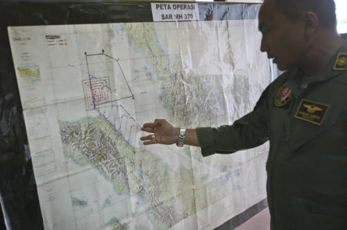 """Lt. Col Bambang Sudewo, commander of the 5th Air Squadron """"Black Mermaids"""" examines a map following a search operation for the missing Malaysia Airlines Boeing 777 that was conducted over the Strait of Malacca, at Suwondo air base in Medan, North Sumatra, Indonesia, Friday, March 14, 2014. The jetliner vanished nearly a week ago with 239 people aboard. (AP Photo/Binsar Bakkara)"""