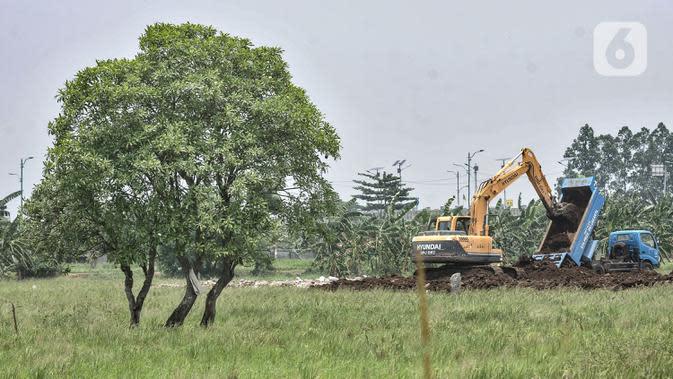 Petugas dari Dinas Bina Marga menggunakan kendaraan alat berat saat menyelesaikan penggarapan lahan untuk dijadikan lokasi pemakaman khusus Covid-19 di Rorotan, Jakarta, Selasa (29/9/2020). Lokasi pemakaman khusus Covid-19 ini memiliki Lahan seluas 2 hektare. (merdeka.com/Iqbal S. Nugroho)