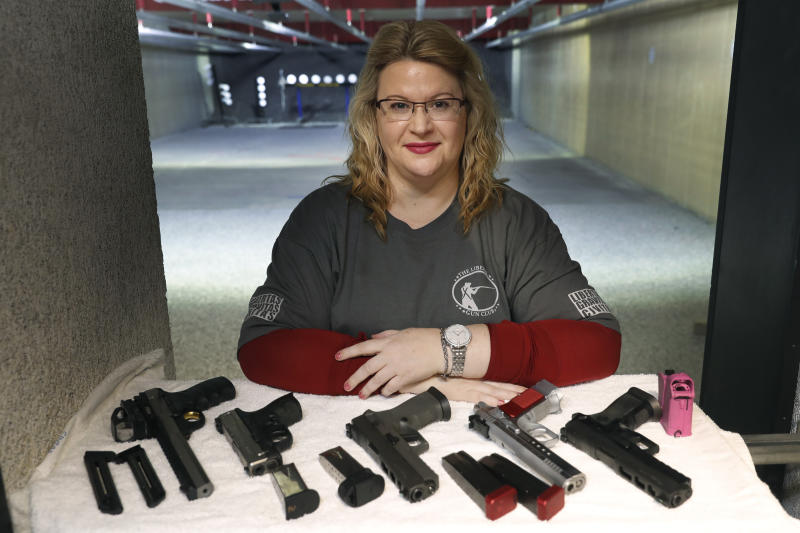 In this Wednesday, Feb. 5, 2020, photo, Kat Ellsworth of Chicago, poses for a portrait with five of the seven guns she owns at the Caliber Tactical Gun Range in Waukegan, Ill. Ellsworth was firmly against firearms and favored gun-control until just a few years ago when she went with a friend to a gun range and discovered a love for firearms and shooting. (AP Photo/Charles Rex Arbogast)