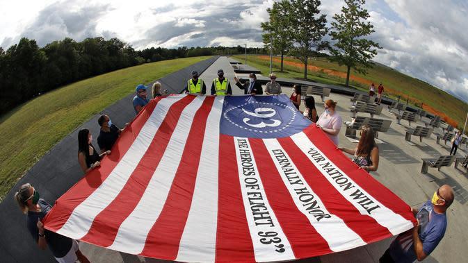 Pengunjung ke Peringatan Nasional Penerbangan 93 di Shanksville, Pa., Berpartisipasi dalam upacara peringatan pada hari Kamis, 10 September 2020, saat negara bersiap untuk menandai peringatan 19 tahun serangan 11 September 2001. (AP Photo/Gene J. Puskar)