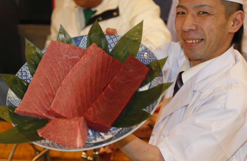 An employee of Kiyomura Co. shows off fillet of a bluefin tuna the company bought at the year's celebratory first auction before being served at its sushi restaurant near Tsukiji fish market in Tokyo, Sunday, Jan. 5, 2014. Sushi restauranteur Kiyoshi Kimura paid 7.36 million yen (about $70,000) for the 507-pound (230-kilogram) bluefin tuna in the auction, just one-twentieth of what he paid a year earlier despite signs the species is in serious decline. (AP Photo/Shizuo Kambayashi)