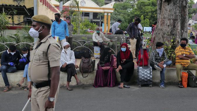 Calon penumpang mengenakan masker saat menunggu kereta di luar stasiun di Hyderabad, India, Jumat (17/7/2020). India melewati 1 juta kasus virus corona COVID-19 atau tertinggi ketiga di dunia setelah Amerika Serikat dan Brasil. (AP Photo/Mahesh Kumar A.)