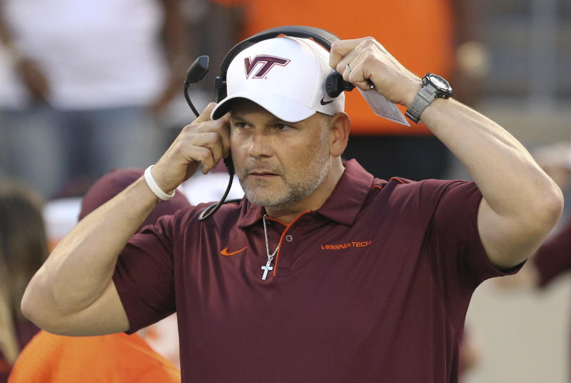 Virginia Tech head coach Justin Fuente puts on his headset at the start of an NCAA college football game against Duke, Friday, Sept. 27, 2019, in Blacksburg, Va. (Matt Gentry/The Roanoke Times via AP)