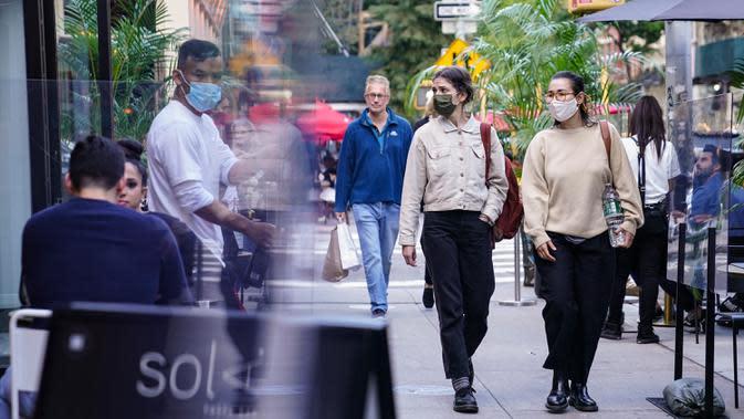 Orang-orang melewati pengunjung di luar restoran yang menawarkan layanan area outdoor di New York pada 3 Oktober 2020. Kota itu mengizinkan restoran membuat area makan outdoor hingga ke trotoar dan jalanan sebagai upaya mengatasi dampak ekonomi COVID-19 yang berkelanjutan. (AP Photo/John Minchillo)