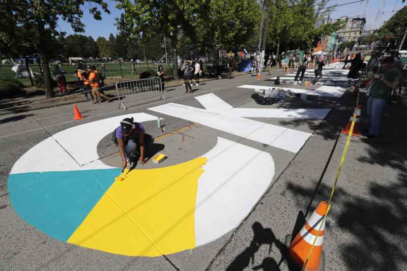 """An artist paints one of the large letters that read """"Black Lives Matter"""" on a street near Cal Anderson Park, Thursday, June 11, 2020, inside what is being called the """"Capitol Hill Autonomous Zone"""" in Seattle. Following days of violent confrontations with protesters, police in Seattle have largely withdrawn from the neighborhood, and protesters have created a festival-like scene. (AP Photo/Ted S. Warren)"""