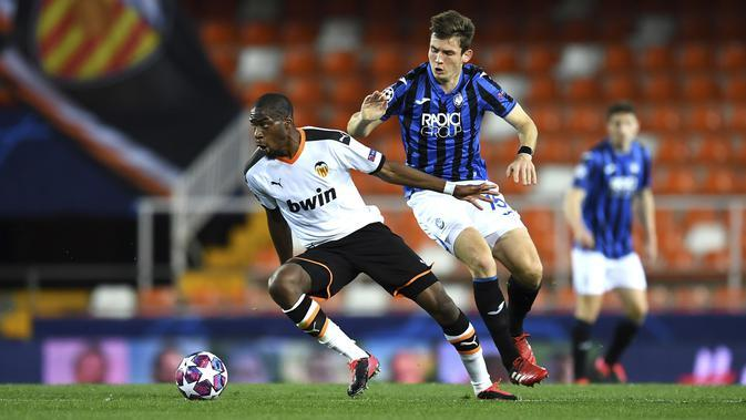 Gelandang Valencia, Geoffrey Kondogbia membawa bola dari kawalan pemain Atalanta, Marten de Roon pada pertandingan leg kedua babak 16 besar Liga Champions di Mestalla, Spanyol (10/3/2020). Atalanta menang 4-3 atas Valencia dan lolos ke perempat final Liga Champions. (UEFA via AP)
