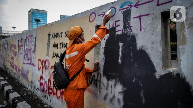 Petugas PPSU membersihkan coretan yang mengotori pembatas jalan pascaunjuk rasa di kawasan DPR/MPR, Jakarta, Jumat (17/7/2020). Coretan tersebut dilakukan oleh massa yang menolak RUU Omnibus Law Cipta Lapangan Kerja di depan Gedung DPR pada Kamis (16/7) kemarin. (Liputan6.com/Faizal Fanani)