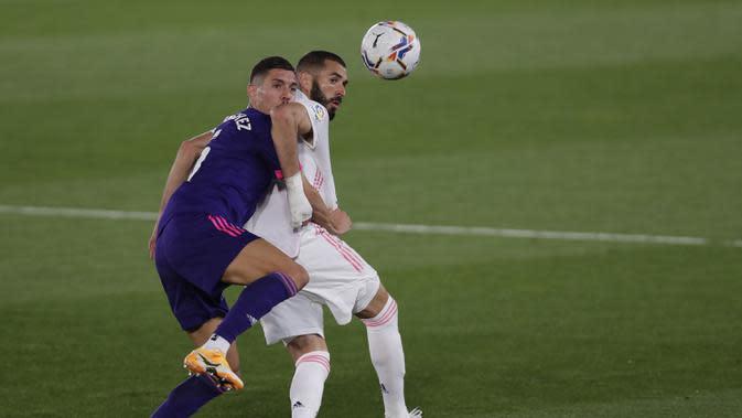 Penyerang Real Madrid, Karim Benzema, berebut bola dengan bek Real Valladolid, Javi Sanchez, pada laga lanjutan Liga Spanyol di Estadio Alfredo Di Stefano, Kamis (1/10/2020) dini hari WIB. Real Madrid menang 1-0 atas Valladolid. (AP Photo/Manu Fernandez)