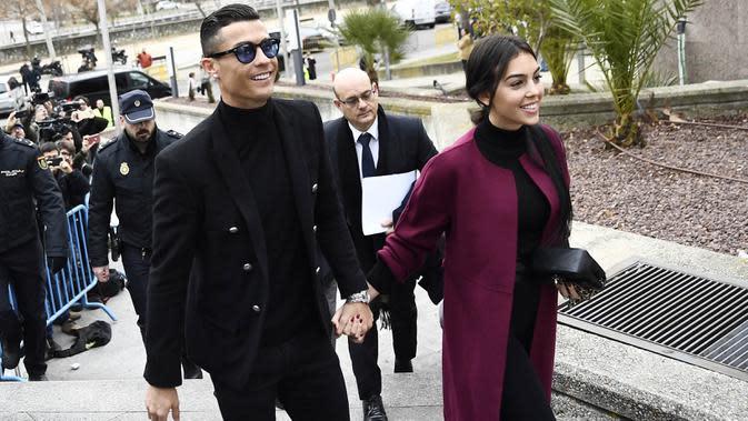 Cristiano Ronaldo bersama kekasihnya, Georgina Rodriguez, tiba di kantor pengadilan untuk menghadiri sidang penggelapan pajak di Madrid, Spanyol (22/2/2019). (AFP/Oscar Del Pozo)