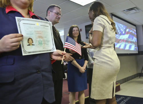 "Immaculee Ilibagiza, right, receives her citizenship certificate during the U.S. Citizenship and Immigration Services naturalization ceremony on Wednesday, April 17, 2013 in New York. ""Who would know that this fantasy would finally happen,"" said Ilibagiza, author of the best seller ""Left to Tell, Discovering God Amidst the Rwandan Holocaust."" She sought asylum in the U.S. after fleeing the 1994 Rwandan genocide, which claimed more than 500,000 lives. (AP Photo/Bebeto Matthews)"
