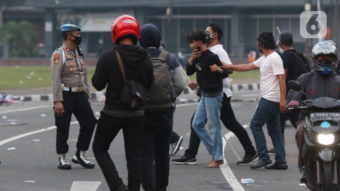 Polisi berpakaian kaus putih mengamankan seseorang yang dicurigai terlibat kericuhan di kawasan Tugu Tani, Jakarta, Selasa (13/10/2020). Sejumlah pemuda diamankan polisi karena dicurigai terlibat kericuhan di kawasan Tugu Tani. (Liputan6.com/Helmi Fithriansyah)