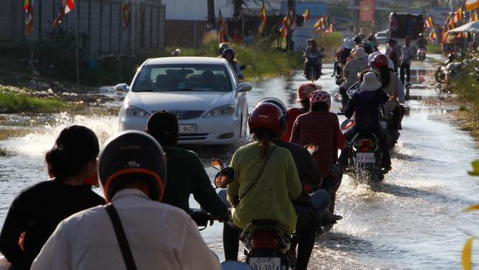 Penduduk desa mengendarai sepeda motor mereka di jalan banjir di desa Trapang Anchanh, di luar Phnom Penh, Kamboja, (27/10). (AP Photo/Heng Sinith)