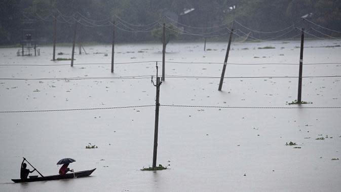Penduduk desa mendayung perahu-perahu desa melalui genangan air di distrik Morigaon di Assam, India (26/6/2020). Banjir disebabkan meluapnya Sungai Brahmaputra akibat hujan yang terus turun. (AP Photo/Anupam Nath)