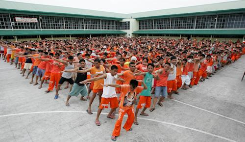 "FILE - In this Aug. 8, 2007 file photo, Filipino inmates practice their dance steps for the ""Together in Electric Dreams"" song, a carefully chosen homage to the inmates' fans, at the Cebu Provincial and Rehabilitation Center in Cebu city, central Philippines. The Filipino inmates whose choreographed ""Thriller"" dance has attracted 52 million YouTube hits since 2007 are getting their own stories told in a movie. Director Marnie Manicad said the action drama ""Dance of the Steel Bars"" was shot in the Cebu provincial prison, the same place where the inmates dressed in orange uniforms danced to global fame. Manicad co-directed the movie with Cesar Apolinario. It will be released in June. (AP Photo/Aaron Favila, File)"