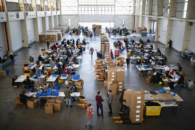 Workers, wearing personal protective equipment, build splash guards during a mass manufacturing operation to supply New York City government with protection to distribute against COVID-19, Friday, March 27, 2020, at the Brooklyn Navy Yard in New York. The new coronavirus causes mild or moderate symptoms for most people, but for some, especially older adults and people with existing health problems, it can cause more severe illness or death. (AP Photo/John Minchillo)