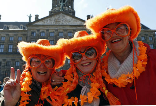 Visitors from Sydney, Australia wearing the Dutch national colors pose for photographers outside the Royal Palace in downtown Amsterdam, Netherlands Monday, April 29, 2013. Queen Beatrix has announced she will relinquish the crown on April 30, 2013, after 33 years of reign, leaving the monarchy to her son Crown Prince Willem-Alexander. (AP Photo/Vincent Jannink)
