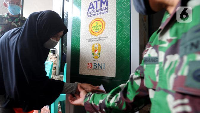 Warga menggunakan ATM Pertanian Si Komandan untuk mendapatkan beras gratis di Kodim 0606/Kota Bogor, Jawa Barat, Minggu (26/4/2020). ATM beras menyediakan 1,5 ton beras per harinya untuk 1000 warga sebagai upaya membantu masyarakat miskin yang terkena dampak Covid-19. (merdeka.com/Arie Basuki)