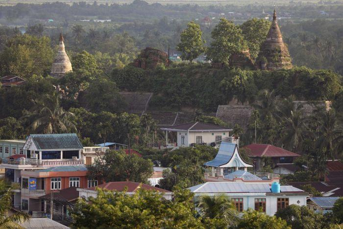 A landscape view of trees, houses, huts and pagodas.