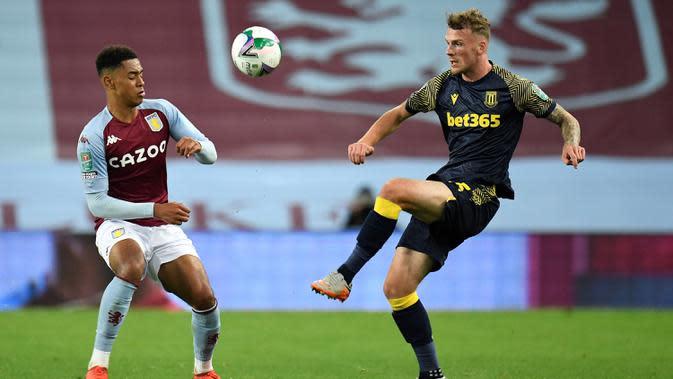Gelandang Aston Villa, Jacob Ramsey, berebut bola dengan bek Stoke City, Josh Tymon, pada laga Piala Liga Inggris di Stoke City, Jumat (2/10/2020) dini hari WIB. Aston Villa kalah 0-1 atas Stoke City. (AFP/Peter Powell/pool)