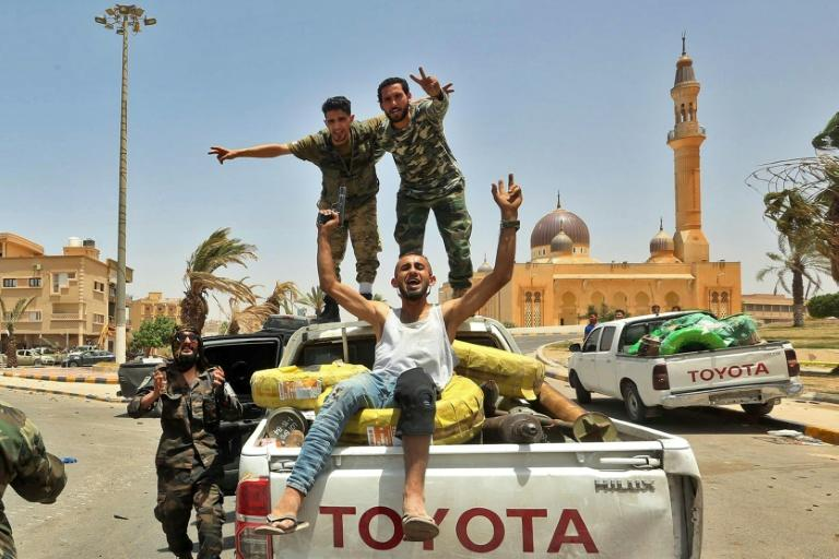 Fighters loyal to Libya's UN-recognised Government of National Accord (GNA) celebrate on the back of a pickup in Tarhuna, southeast of the capital Tripoli, on June 5 after seizing the town