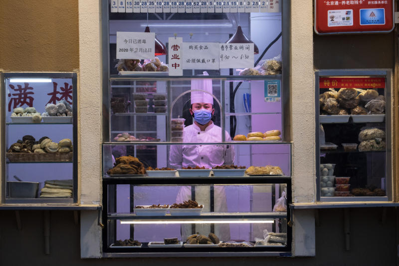 In this photo taken Saturday, Feb. 22, 2020, a chef looks out from behind a display of food products at a restaurant in Beijing, China. Regulators on Monday promised tax cuts and other aid to help companies recover from China's virus outbreak and expressed confidence the ruling Communist Party's growth targets can be achieved despite anti-disease controls that shut down much of the economy. (AP Photo/Ng Han Guan)