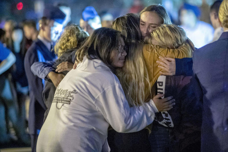 People hug each other during a vigil for the Saugus High School shooting victims at Central Park, Thursday, Nov. 14, 2019, in Santa Clarita, Calif. Los Angeles County sheriff's officials say a 16-year-old student shot several classmates and then himself in a quad area of Saugus High School Thursday morning. (Hans Gutknecht/The Orange County Register/SCNG via AP)