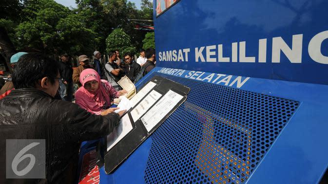 Warga mengisi formulir di Gerai Samsat Keliling di Jalan Kalibata Raya, Jakarta, Senin (11/7). Pasca libur lebaran 2016, gerai Samsat Keliling kembali beroperasi melayani pembayaran pajak kendaraan bermotor. (Liputan6.com/Helmi Fithriansyah)