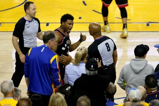 Toronto's Kyle Lowry complains to referee Marc Davis after being pushed by Golden State Warriors minority investor Mark Stevens during an NBA Finals game Wednesday