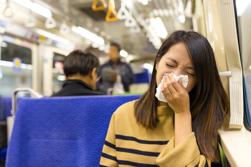 woman sick and sneezing on the bus