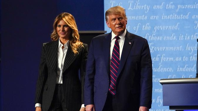 Presiden Donald Trump bersama ibu negara Melania Trump berdiri di atas panggung setelah debat presiden pertama dengan calon presiden dari Partai Demokrat, mantan Wakil Presiden Joe Biden Case Western University dan Cleveland Clinic, di Cleveland, Ohio, Selasa, 29 September 2020. (AP Photo/Julio Cort