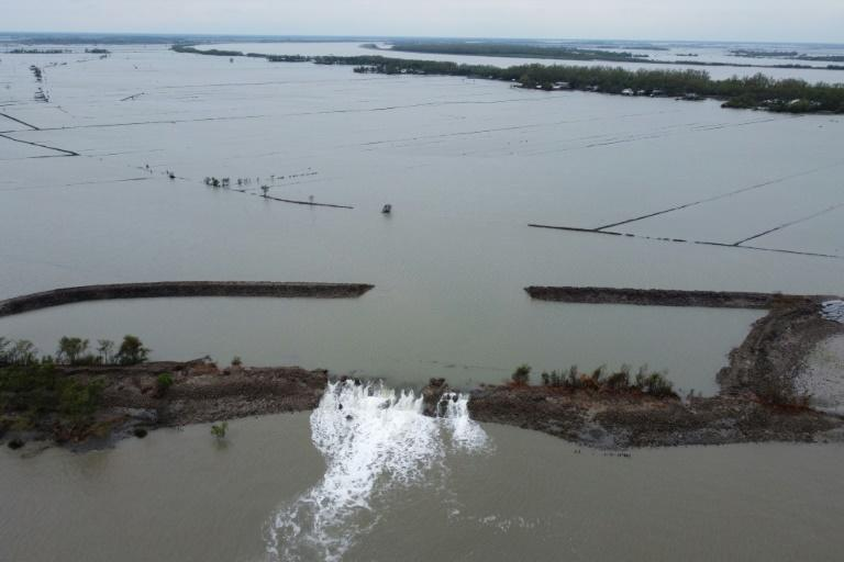 An aerial view shows water from a flooded crab farming area (top) breaking through a damaged dam following the landfall of Cyclone Amphan in Burigoalini, Bangladesh, on May 21, 2020