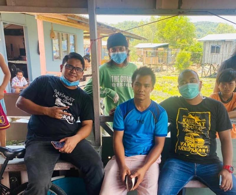 Yunizam (on the right) along with his distribution team with Fendi (middle) at his home. — Photo courtesy of Facebook/Abam Botak