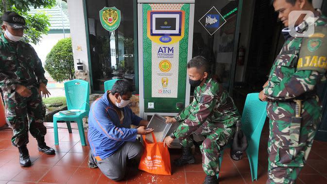 Warga menggunakan ATM Pertanian Si Komandan untuk mendapatkan beras gratis di Kodim 0606/Kota Bogor, Jawa Barat, Minggu (26/4/2020). Kementerian Pertanian bersama Bank BNI, dan TNI AD menempatkan ATM beras gratis di sejumlah Kodim di wilayah Jabodetabek. (merdeka.com/Arie Basuki)