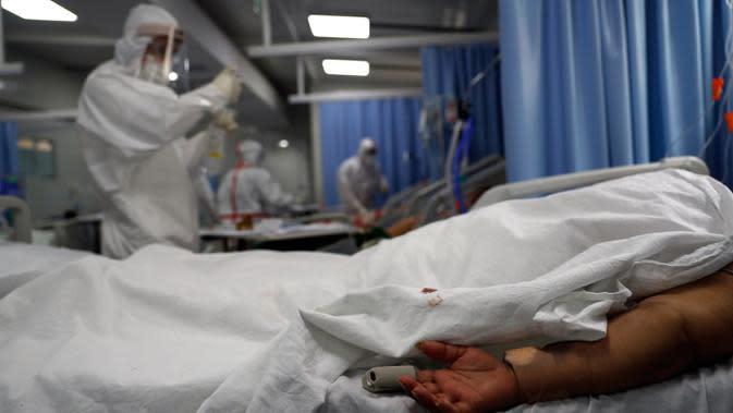 Seorang pasien COVID-19 berbaring telungkup saat perawat menyiapkan suntikan di ICU Rumah Sakit Nasional di Itagua, Paraguay, Senin (7/9/2020). (AP Photo/Jorge Saenz)